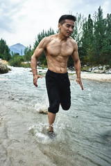 Asian athlete on a morning run on the river, Kazakh jogger in nature close-up