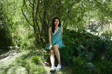 Asian Thai girl in summer dress laughs and smiles while sitting in a green forest