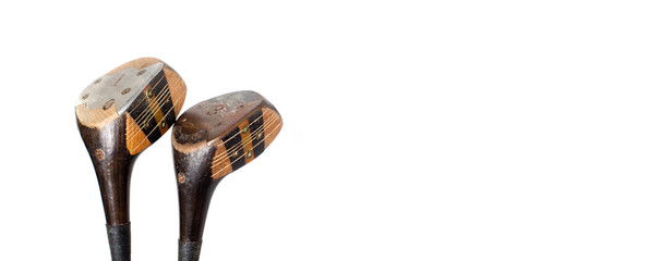 Two vintage golf clubs on white background. Copy space