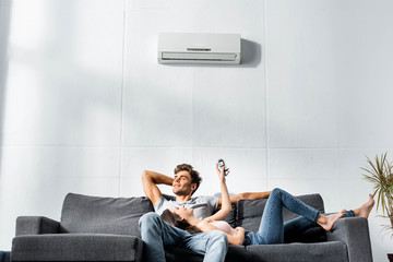 attractive girlfriend switching on air conditioner and lying on legs of handsome boyfriend