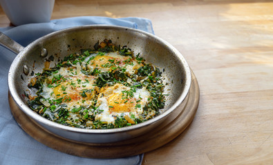 pan with spinach and fried eggs, spices and herb garnish, protein-rich dish for low carb diet on a wooden table, copy space