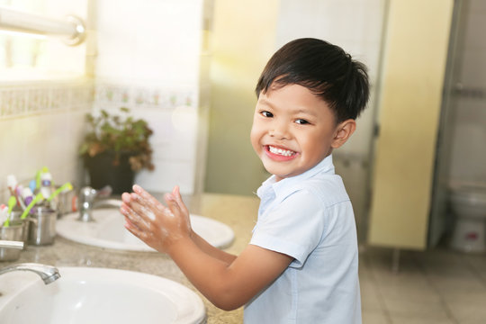 An Asian school boy washing his hand at a faucet sink and water tab in a school.