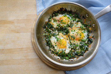 pan with spinach and fried eggs, spices and herb garnish, protein-rich dish for low carb diet on a wooden table, copy space, high angle top view from above