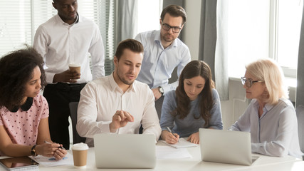 Company employees listening boss sitting at desk in boardroom