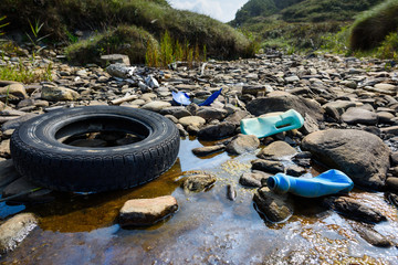 Car tire and plastic bottles in muddy puddle on beach. Beach waste pollution from ocean. Fotobehang