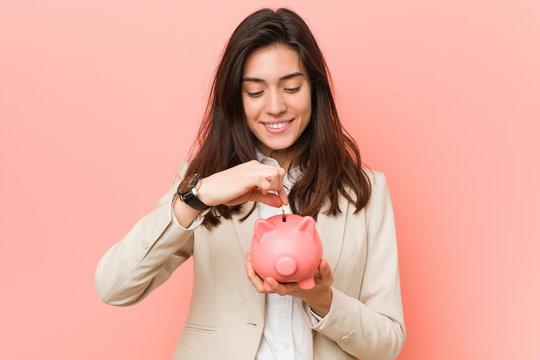 Young caucasian woman holding a piggy bank