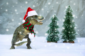 Dinosaur Tyrannosaurus rex ( t-rex ) wearing a Santa Claus hat and scarves have Tree pine snow forest model with snow white background in theme winter Merry christmas and Happy new year.