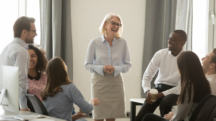 Mature female team leader having fun with coworkers in office