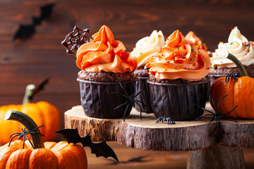 Halloween cupcakes and pumpkins on dark background. Sweets for holiday party.