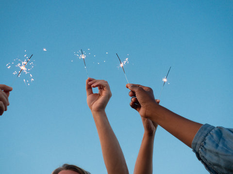 People celebrating special date outside. Hands of men and women holding sparklers over clear sky. Celebration concept