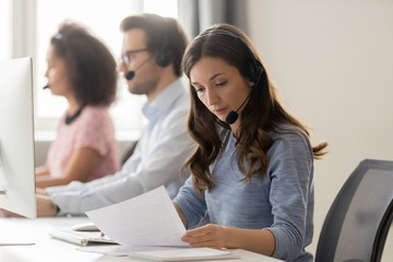 Customer support phone operator sitting at workplace holds read document