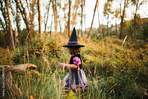 Girl walking disguised as a witch in the woods during Halloween