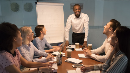 Wall Mural - Corporate team sitting at boardroom listening dark skinned business coach