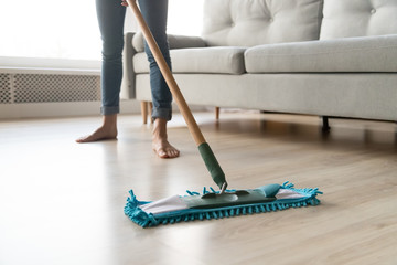 Woman housewife holding mop cleaning floor at home, close up