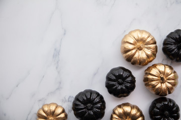 Luxury gold and black autumn pumpkin flat lay composition on a marble background