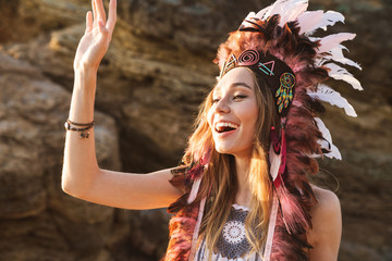 Image of hippy girl in indian chief feather headdress walking by seaside