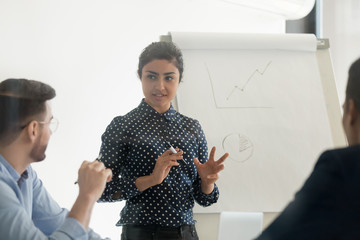 Confident female indian speaker coach training diverse employees group