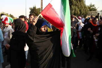 An Iranian woman holds the Iranian flag as she arrives to attend Iran's FIFA World Cup Asian qualifier match against Cambodia, as for the first time women are allowed to watch the national soccer team play in over 40 years, at the Azadi stadium in Tehran
