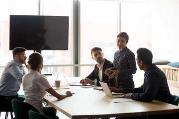 Confident female indian manager leading diverse employees group meeting