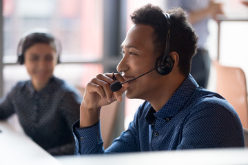 Smiling young african businessman call center agent laugh at workplace
