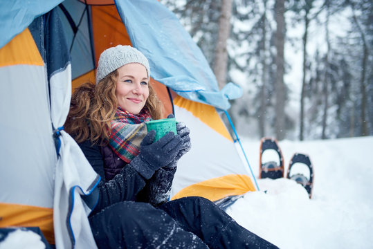 Confident solo woman traveller camping through an evergreen winter forest in Canada