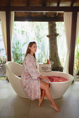 Gorgeous caucasian millennial woman relaxing at tropical hotel spa with serene herbal bath and flower treatment in Bali