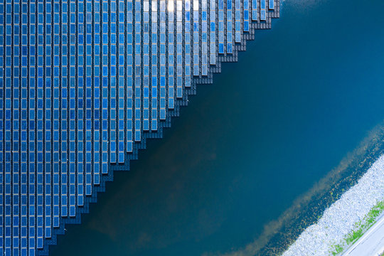 Solar Photovoltaic of solar farm aerial view, solar plant rows array of on the water mount system Installation in earthen pond, water storage