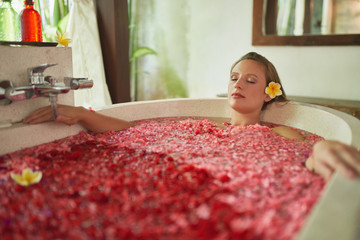 Gorgeous millennial girl pampering herself in modern bath tub filled with flower petals in tropical resort and spa