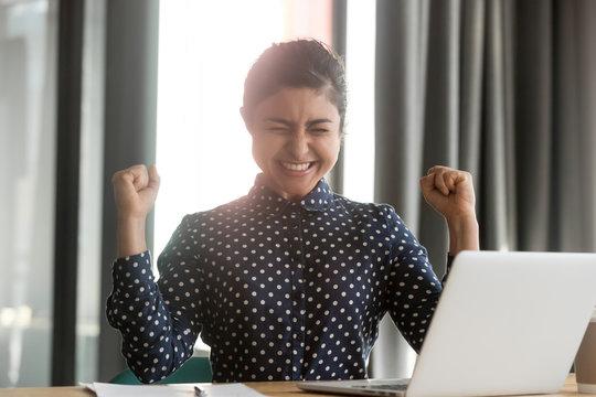Happy overjoyed indian business woman winner celebrate computer win