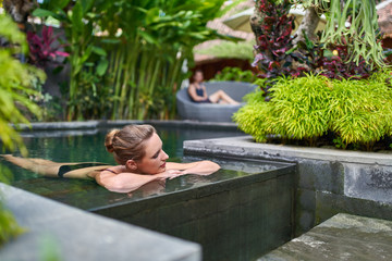 Beautiful peaceful woman relaxing outdoors in sunny and lush stone swimming pool of luxurious hotel during tropical getaway in Bali
