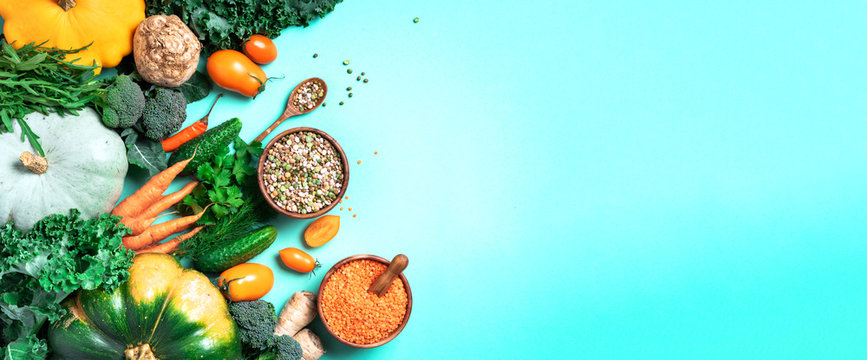 Organic vegetables, lentils, beans, raw ingredients for cooking on trendy green background. Healthy, clean eating concept. Vegan or gluten free diet. Copy space. Top view. Food frame