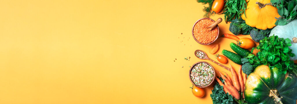 Organic vegetables, lentils, beans, raw ingredients for cooking on trendy yellow background. Healthy, clean eating concept. Vegan or gluten free diet. Copy space. Top view. Food frame