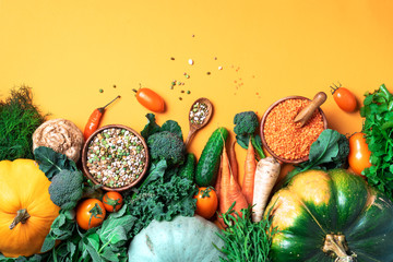 Organic vegetables, lentils, beans, raw ingredients for cooking on trendy yellow background....