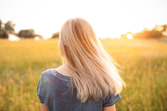 Young woman with blonde hair standing on the field and looking on the sunset