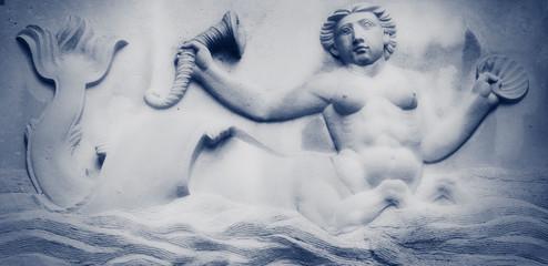 Ancient statue of Mermaid in sea water.