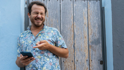 Guy watching a video in social media and laughing with gesturing of enjoying. Happy man reading a good joke in his phone with internet and pointing with his finger
