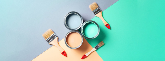 Metal paint cans and paint brushes on multicolor background. Top view. Copy space. Trendy green color concept