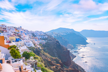 Foto op Plexiglas Santorini Picturesque cityscape of Oia village on Santorini Island with traditional white architecture over the Caldera mountains in Aegean sea at sunset, Greece. Scenic travel background.