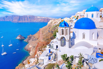Beautiful Oia town on Santorini island, Greece. Traditional white architecture and greek orthodox churches with blue domes over the Caldera in Aegean sea, Greece. Scenic travel background.