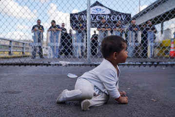 A baby sits near a group of migrants who returned to Mexico to await their U.S. asylum hearing