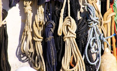 View on isolated knotted boat ropes hanging in a row on ship wall in bright natural sun light