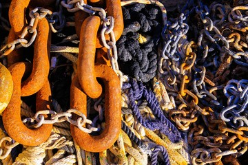 Full frame close up of old rusty brown anchor chain links on bunch of boat ropes in natural sun light