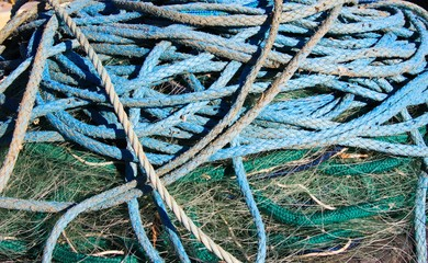 Close up of pile of blue ship ropes on green isolated fishing net
