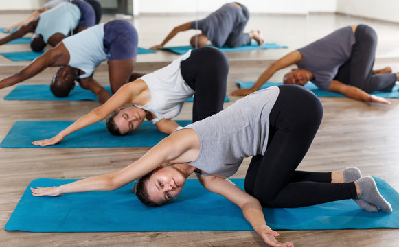 Group of active adult women and men exercising stretching workout