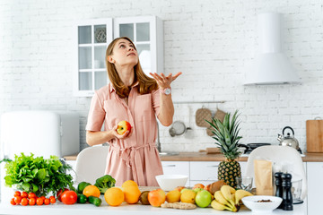 Woman in kitchen ready to prepare meal with vegetables and fruits. Woman with an apple.