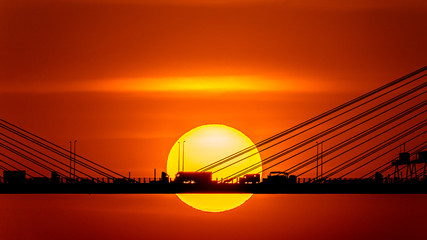Fotomurales - Sunset over the cable-stayed bridge with silhouette of car crossing the sea bay