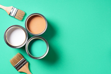 Paint brush and open paint can with on trendy green background. Top view, copy space. Appartment renovation, repair, building and home design concept.