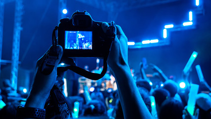 Photographer taking picture with camera at a festival concert with crowd people raised hands and attending a concert. Blue black light by stage lights. Summer music festival concept.
