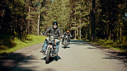 Two bikers are on their bikes riding too fast on the road Wall mural
