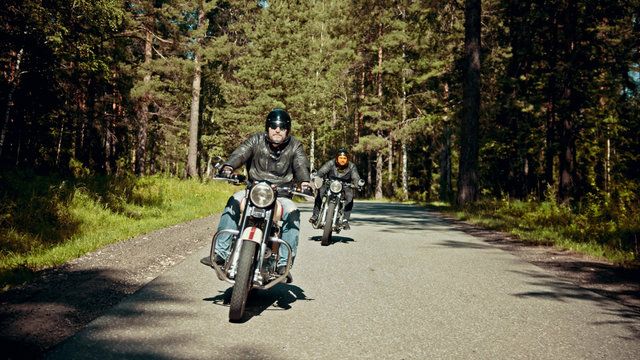 Two bikers are on their bikes riding too fast on the road